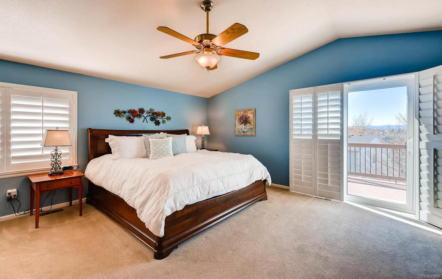 Spacious master bedroom with vaulted ceilings and pajama deck