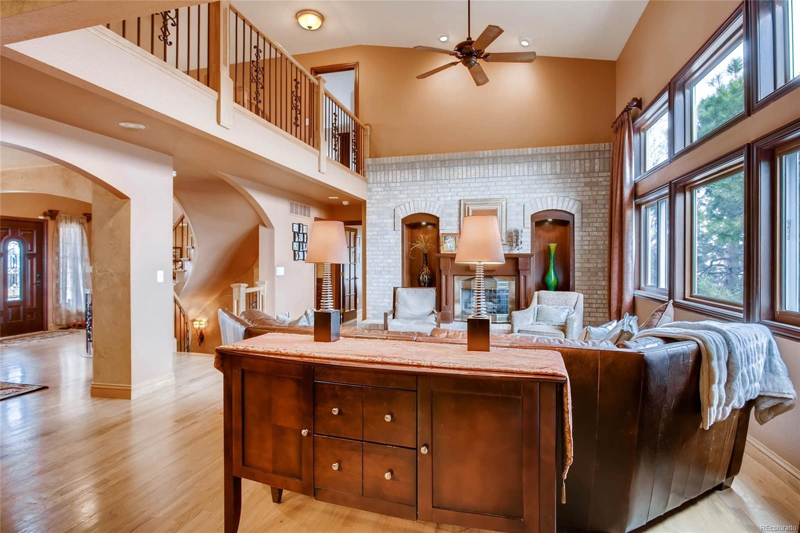 Vaulted two story family room with gorgeous brick hearth and custom wood work sh