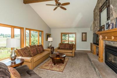 Living Room with Stone Wall and Wall of Windows