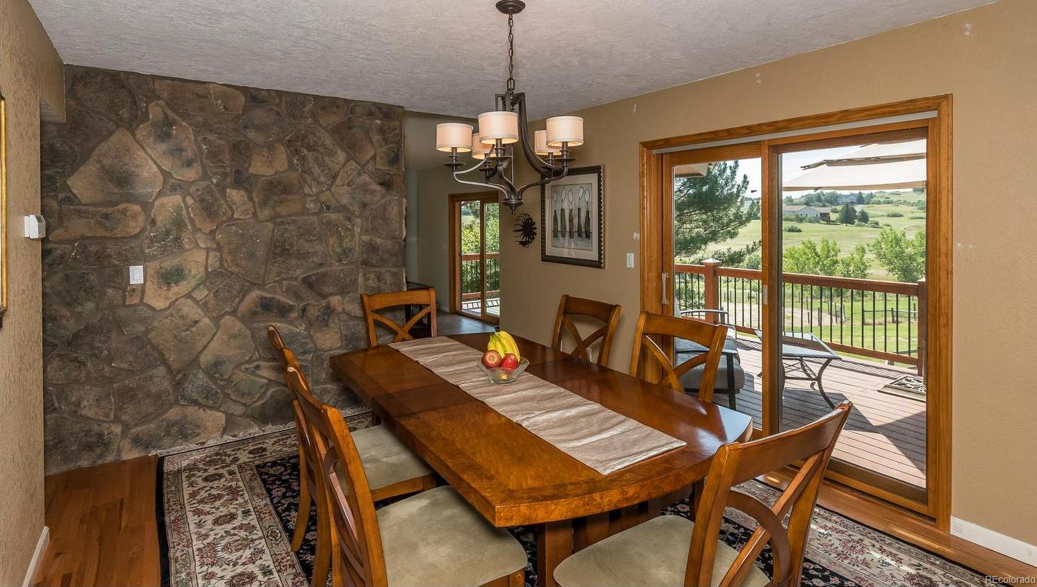 Formal Dining Room with Stone Wall and Wide Plank Floors