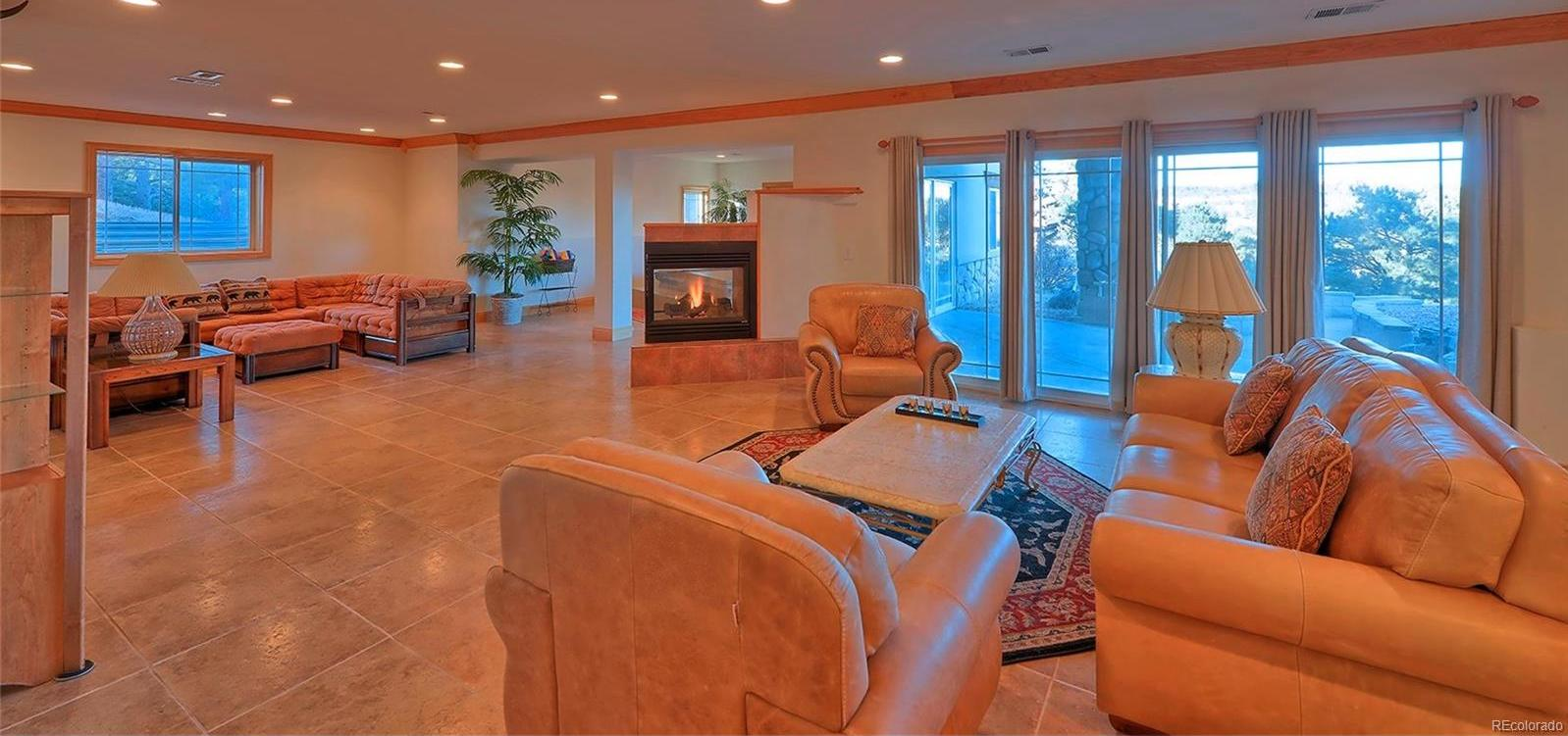 Expansive lower level recreation room, spa, gym & ample storage room across full