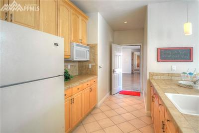 Kitchenette in pool house with eating bar looks out at the pool. The open door l