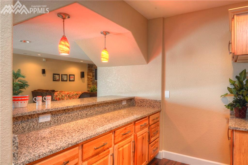 Kitchen in basement with pendant lighting, granite counters open to the media ar