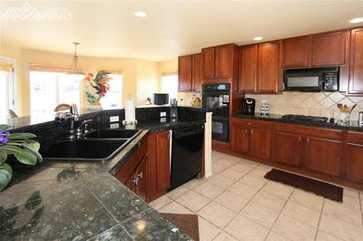 Appliances include double wall ovens & a gas cooktop