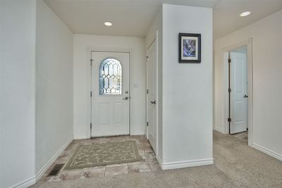 A classic tile entry, paired to a beautiful front door with a leaded glass inser