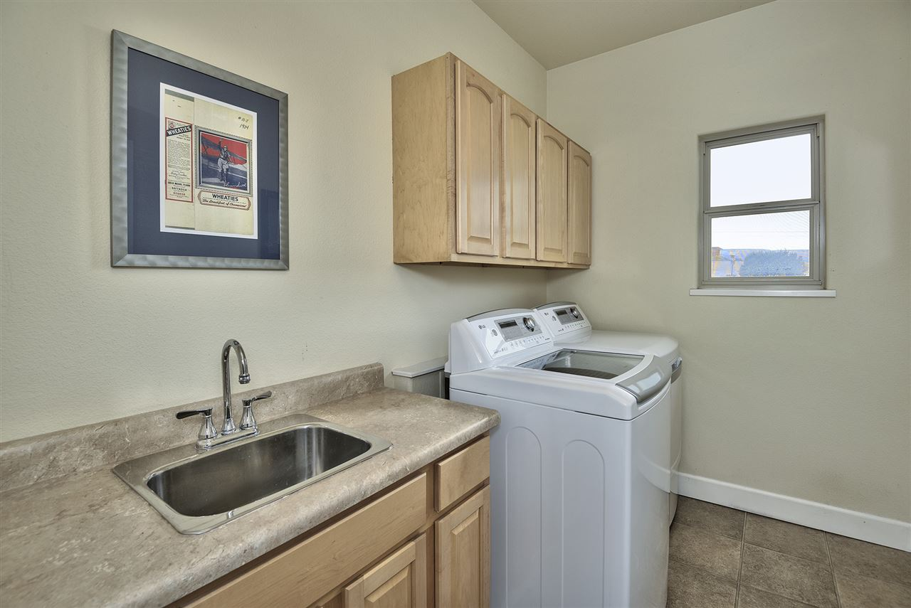 This home's spacious laundry room offers a laundry sink and lots of cabinet stor