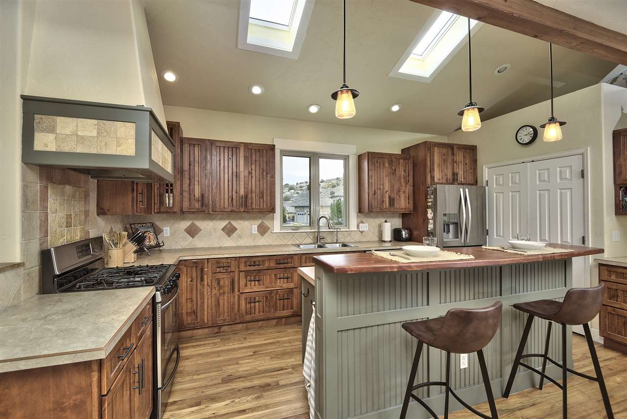 A large double-doored pantry is mated to sunny skylights & custom tile backsplas