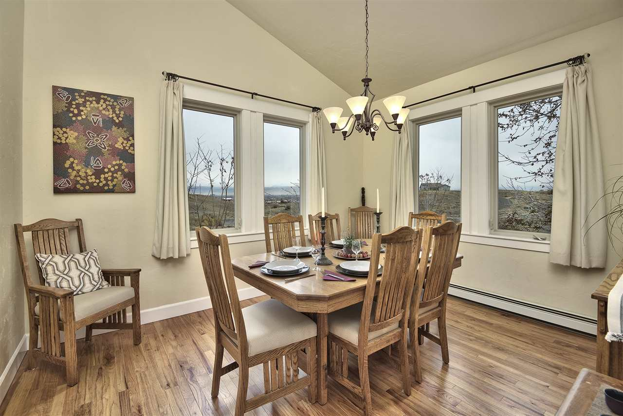 This warm and inviting dining room boasts hardwood flooring and views from two d