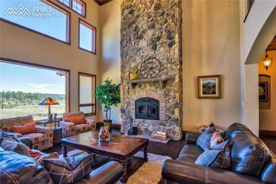 Great Room with floor to ceiling wood burning stone fireplace, hardwood floors a