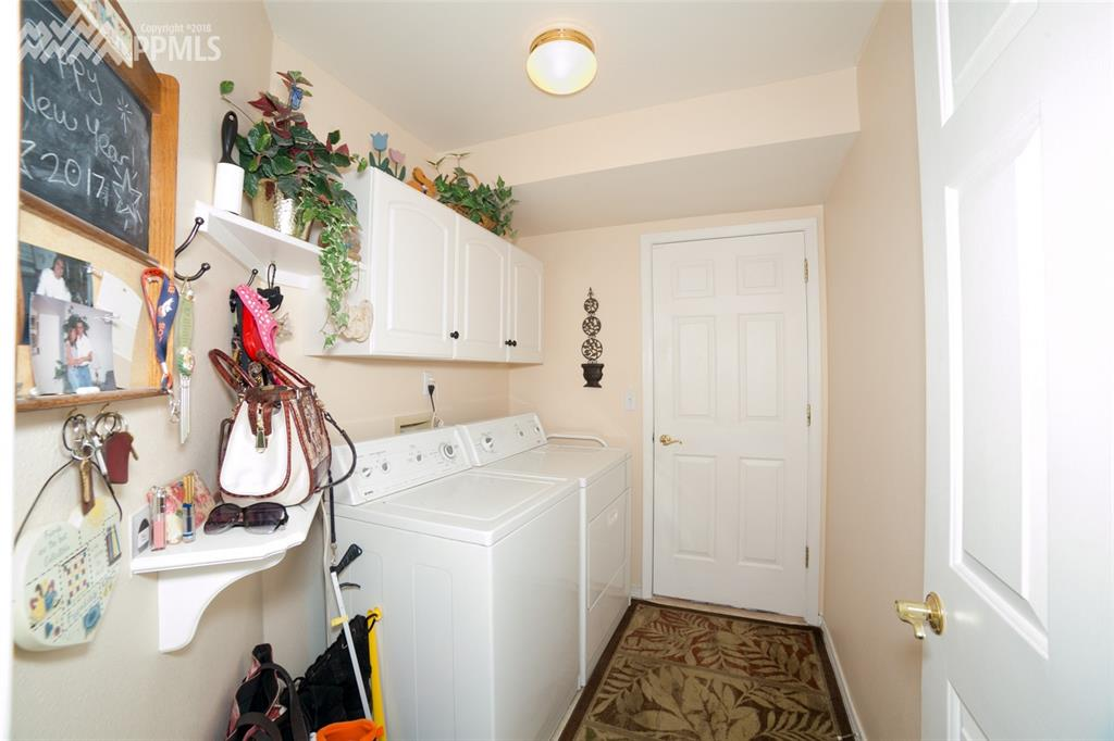 Laundry room, with built in shelving and entry to oversized 2 car garage