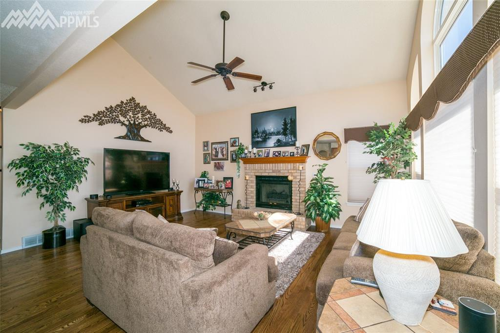 Bright and open living room with vaulted ceilings, ceiling fan and plenty of win