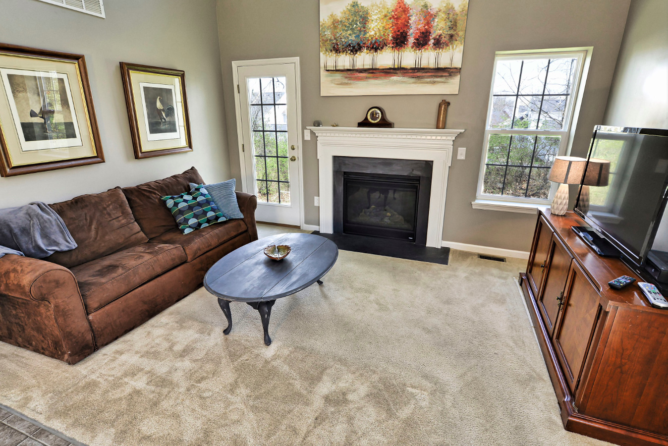 The living room allows for plenty of light to come in. The gas fireplace makes t