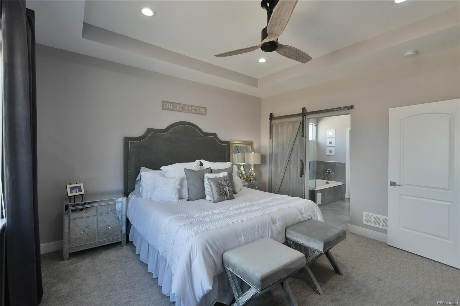 Master bedroom with coffered ceiling, recessed lighting, barn door to bathroom