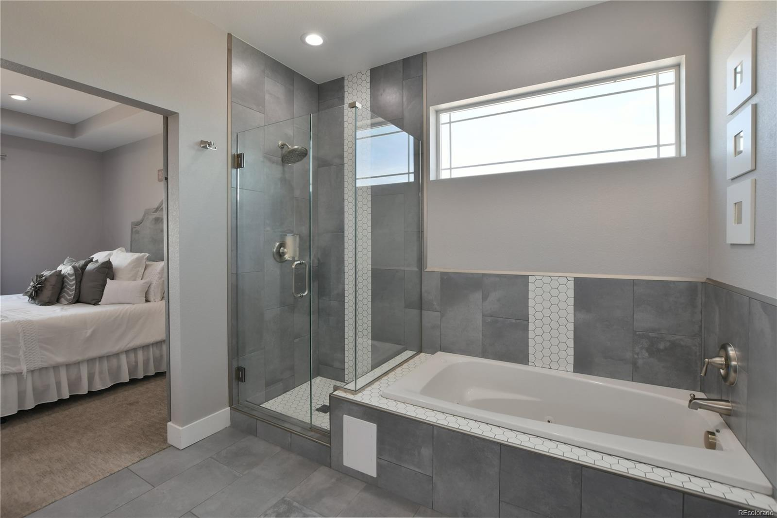 5 piece master bath with upgraded tile in the frameless shower and bathtub