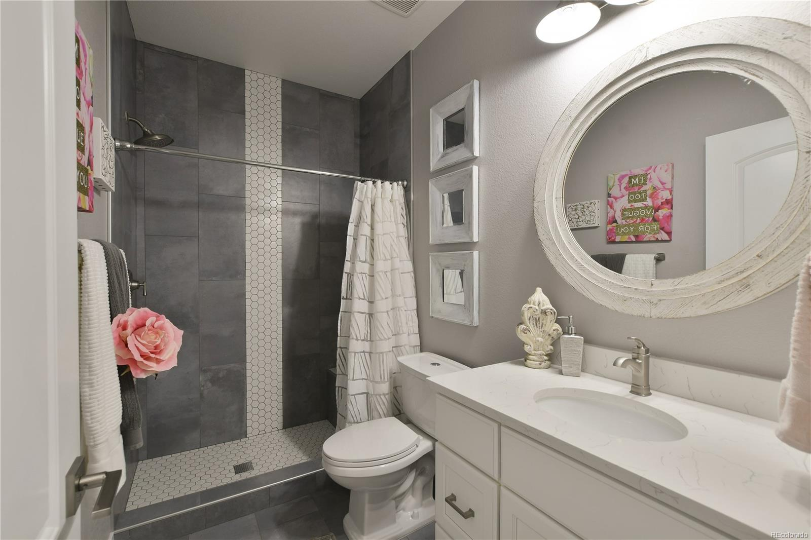 Hall bath with oversized shower, quartz counters and tiled floors.