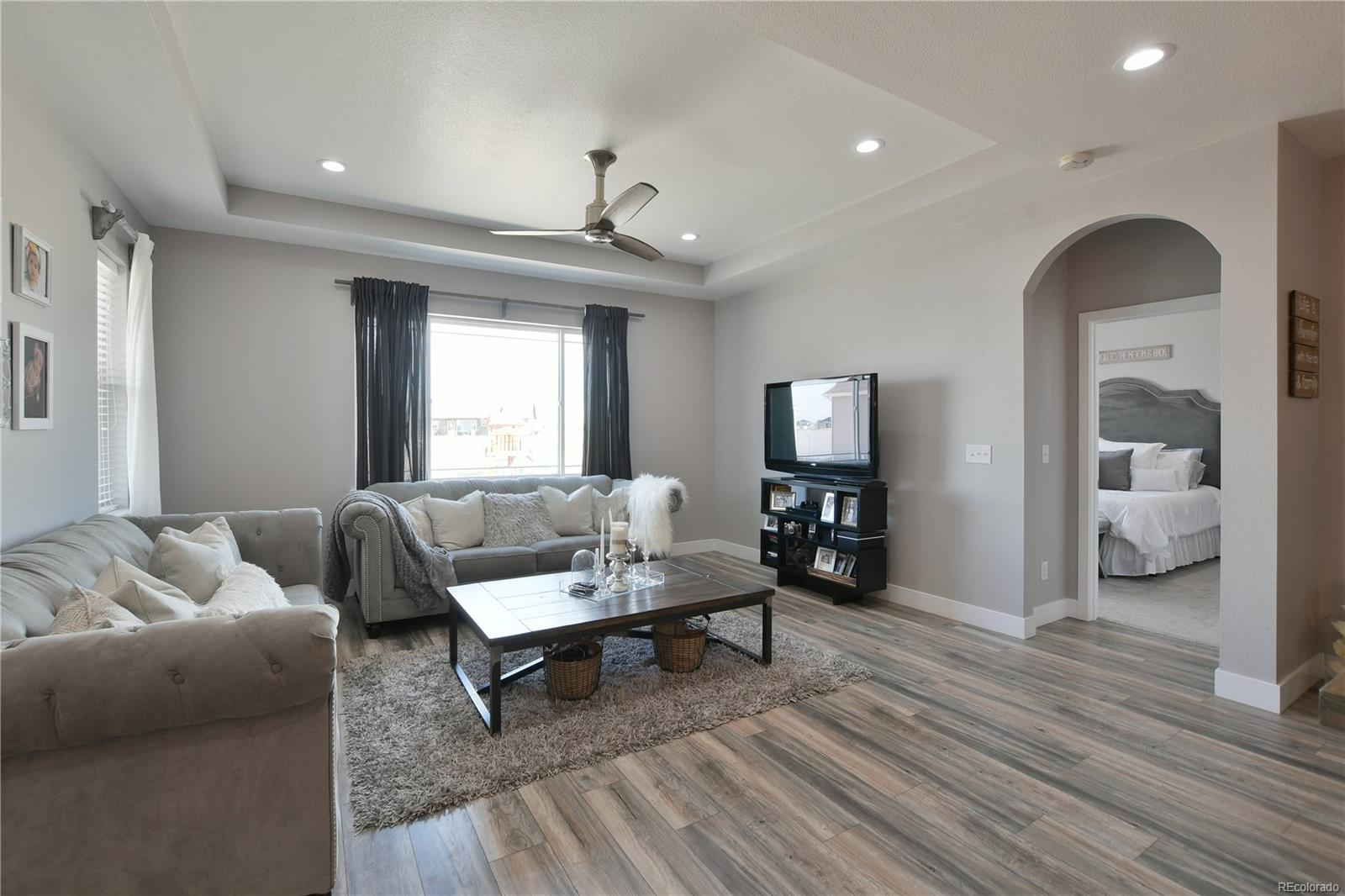 Great room with coffered ceiling, recessed lighting and ceiling fan