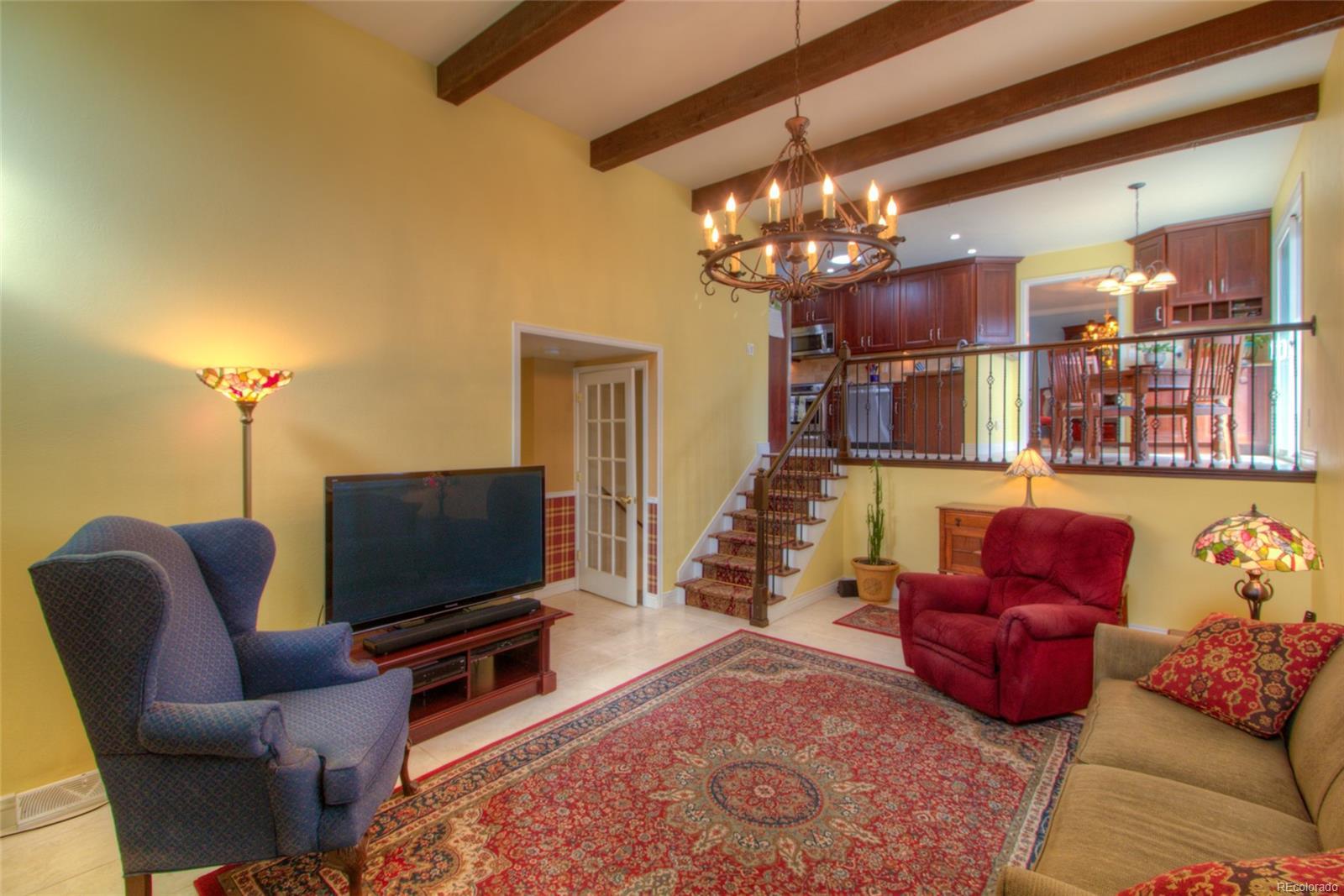 Family Room has tile floors, wood beams and stunning light fixture