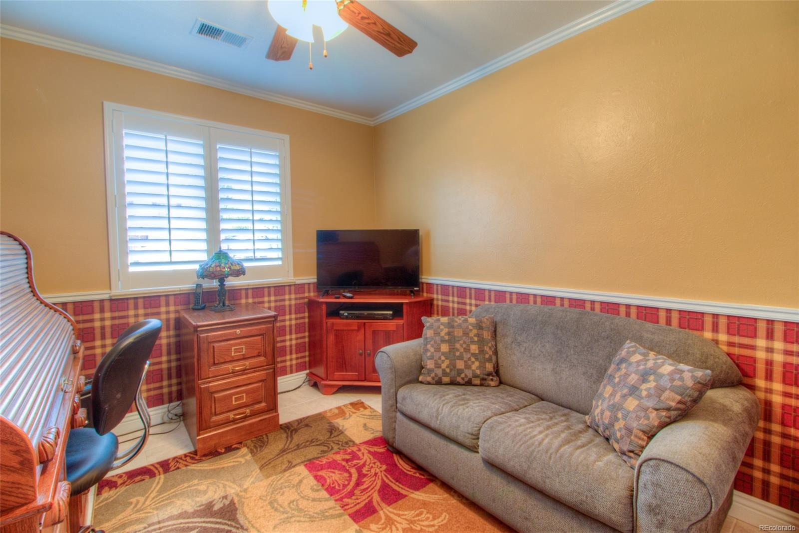 Lower level 4th Bedroom with tile floor, plantation shutters and a walk-in closet