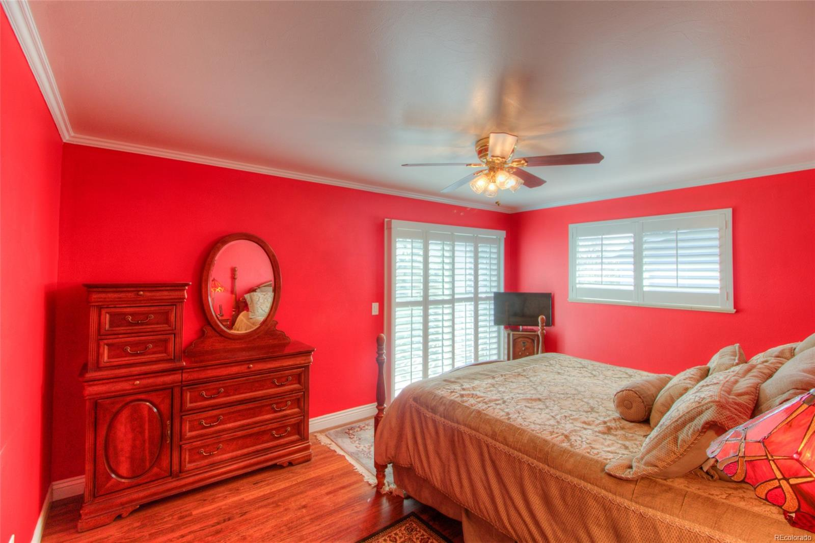 Sunny Master Bedroom with hardwood floors, plantation shutters and crown molding