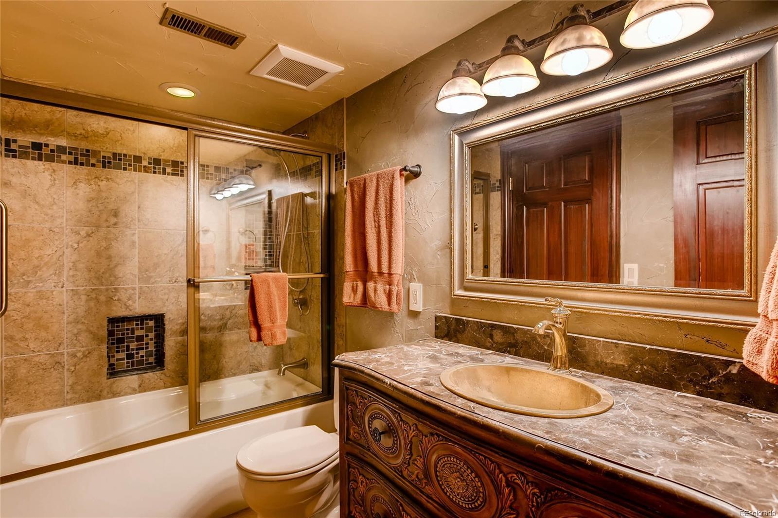 Full bathroom adjacent to bedroom in basement