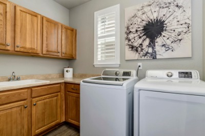 Main Floor Laundry with Utility Sink & Storage