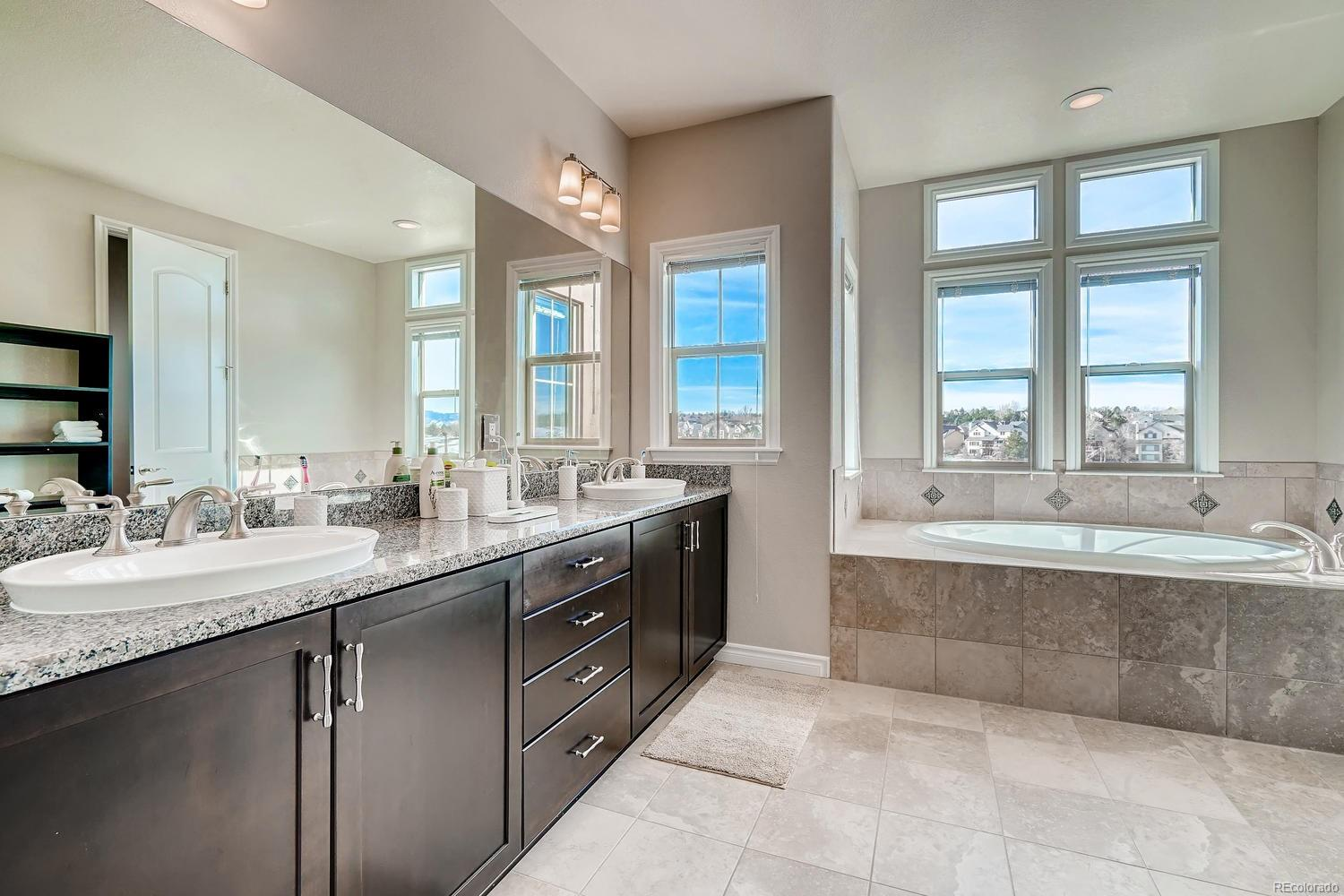 Great light in Master Bath with detailed tile flooring and tub/shower surround.