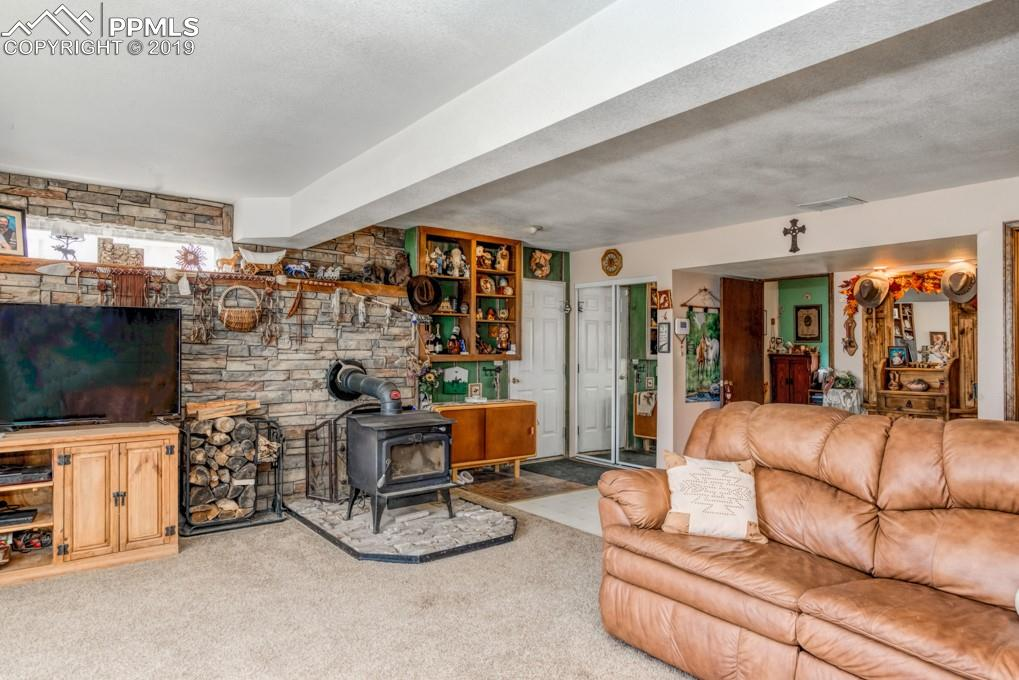 Rustic lower level family room with a wood burning fireplace insert.