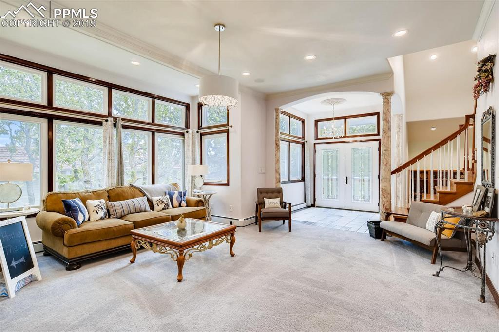 Light filled living area & entry with new doors, chandeliers.
