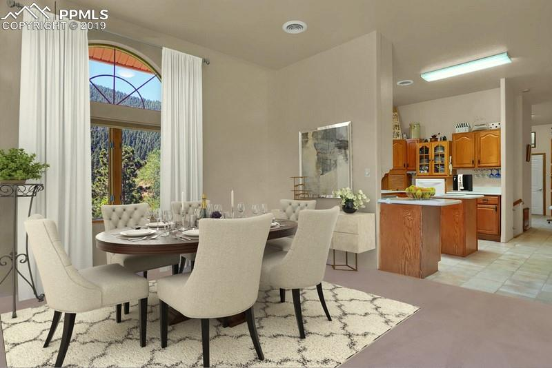 The kitchen has tons of cabinetry, upgraded cabinets and island with white Corian counters.