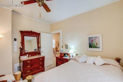Alternate view of north bedroom; neutral colors, solid wood doors and ceiling fan.