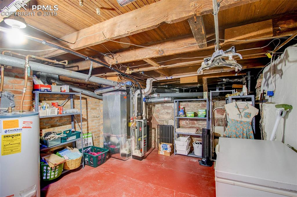 Utility area of basement contains laundry facilities and deep freezer.