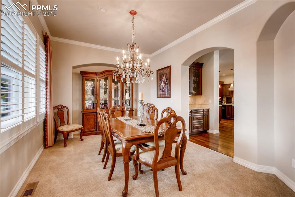 Formal dining room with crown molding  and detailed arched doorways