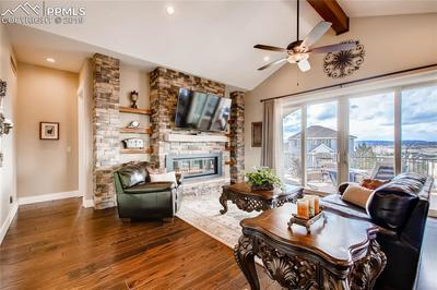 Great room with stone wall and gas fireplace. Plus expansive Pella windows throu