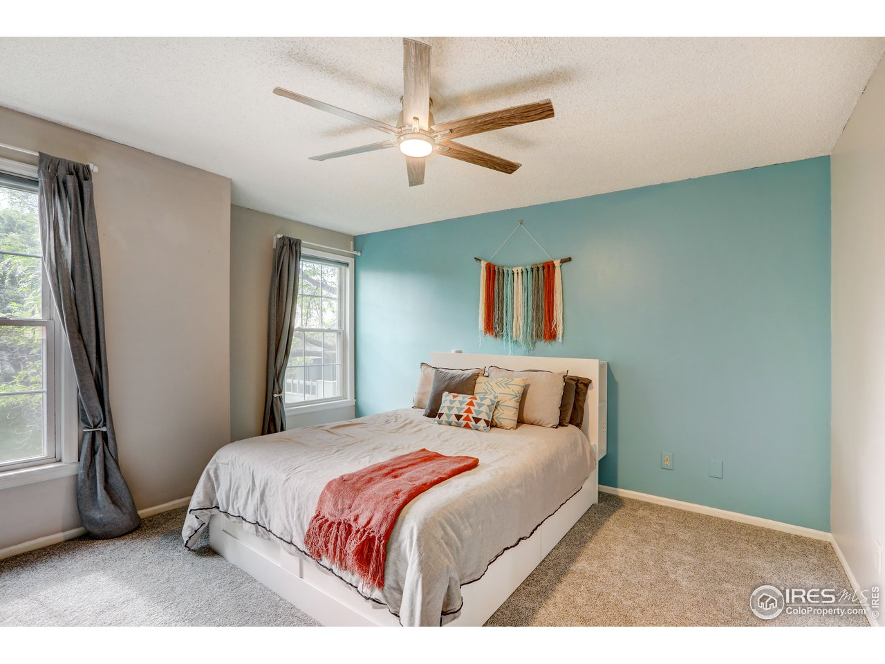 Primary bedroom with new carpet and ceiling fan with remote