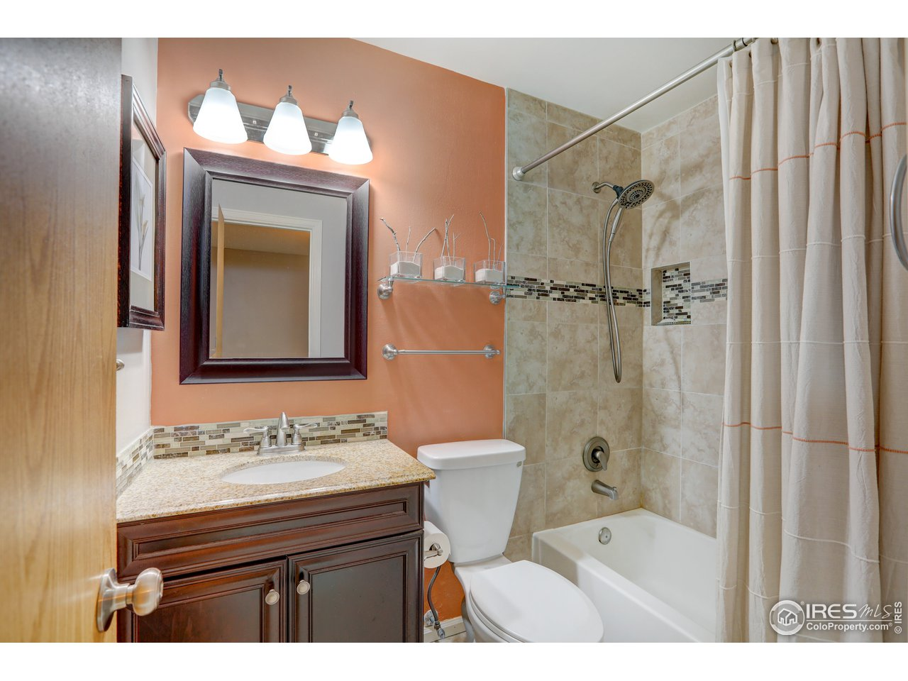 upgraded Hall bath with tile floor, under mount sink and stylish tile tub surround