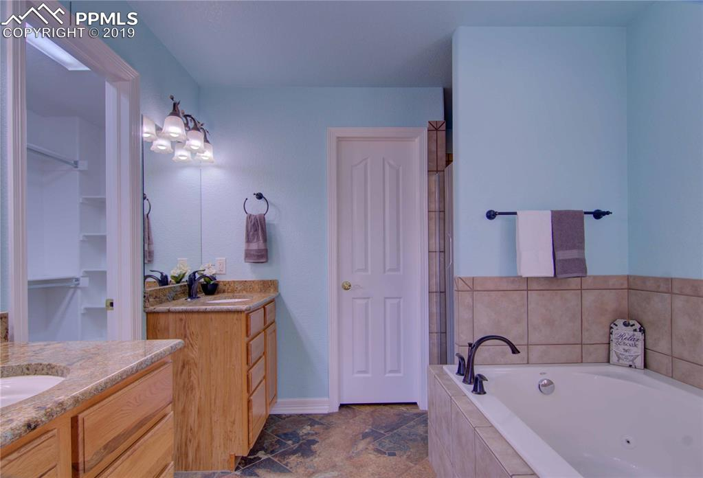 Master private 5-piece bath with granite counters, tile flooring, private toilet area, and walk-in closet.