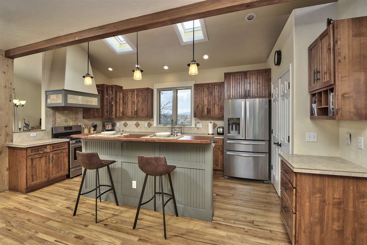 Lantern droplights and a butcher block island breakfast bar are paired to exposed wood beaming!