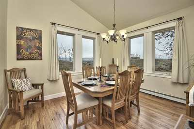 This warm and inviting dining room boasts hardwood flooring and views from two directions!
