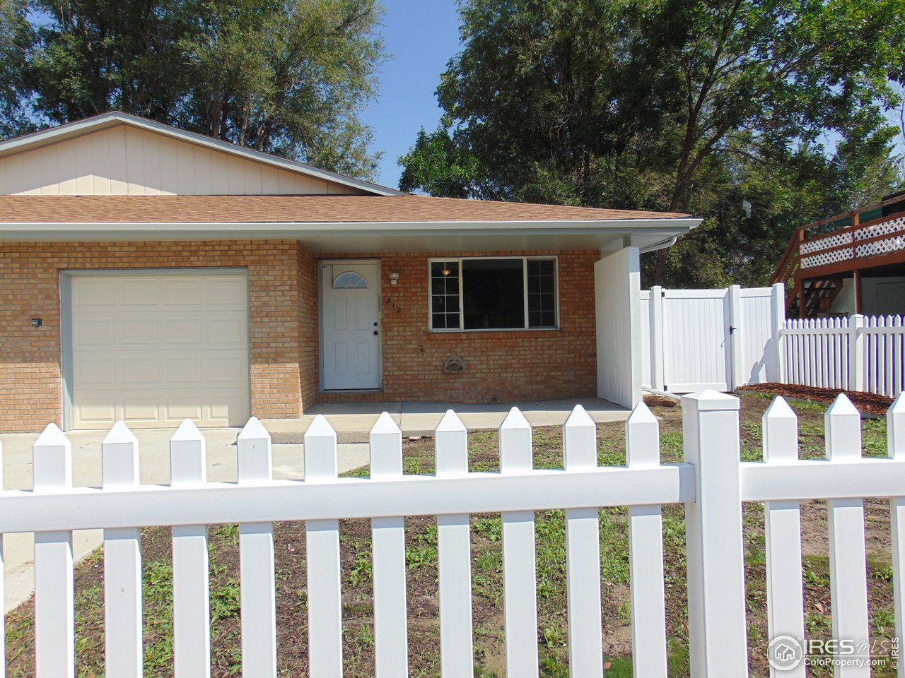 Front with new front picket fence and new driveway. New privacy fence on side and back