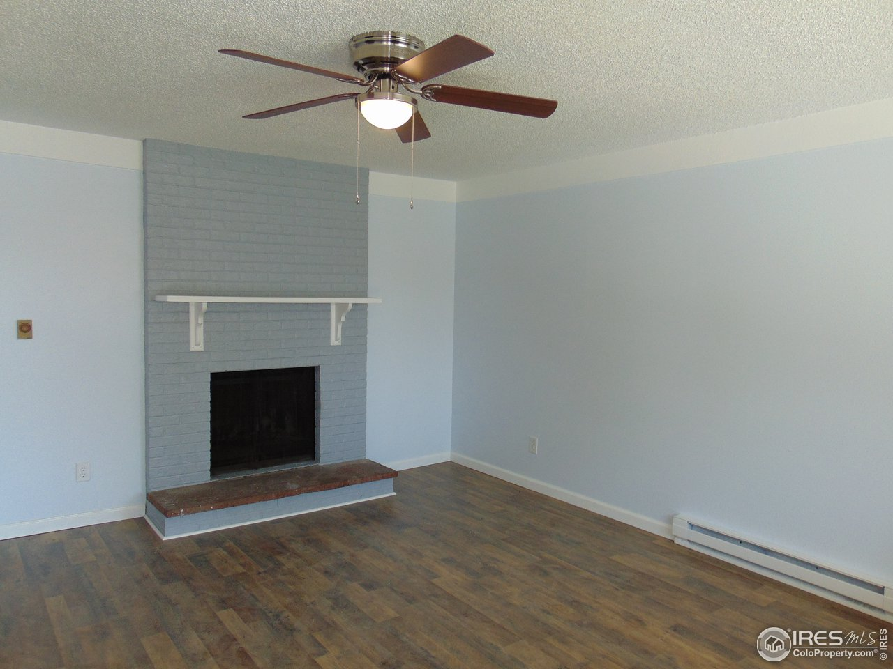 Livingroom with wood burning fireplace and ceiling fan for comfort.