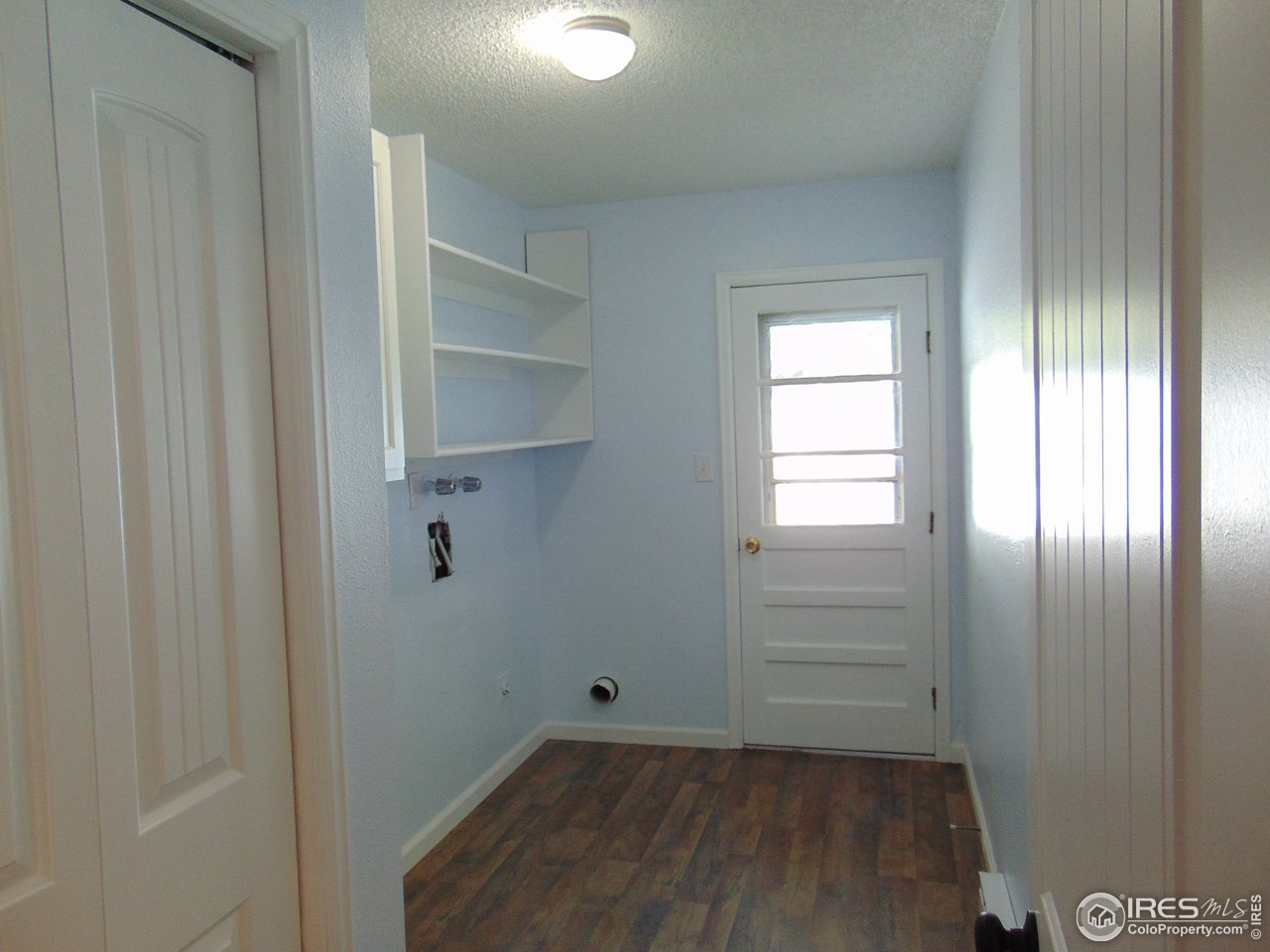 Oversized Laundry room with new flooring, storage cabinet, pantry and easy access to your back yard