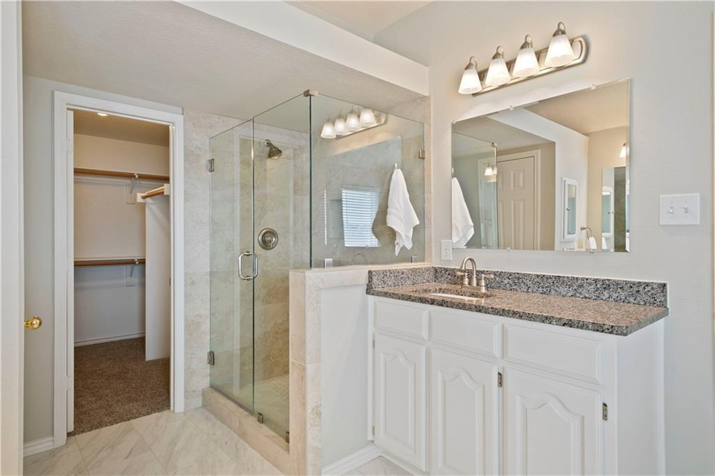 Upgraded soaking tub and view of second lavatory with granite top, brush nickel fixtures.