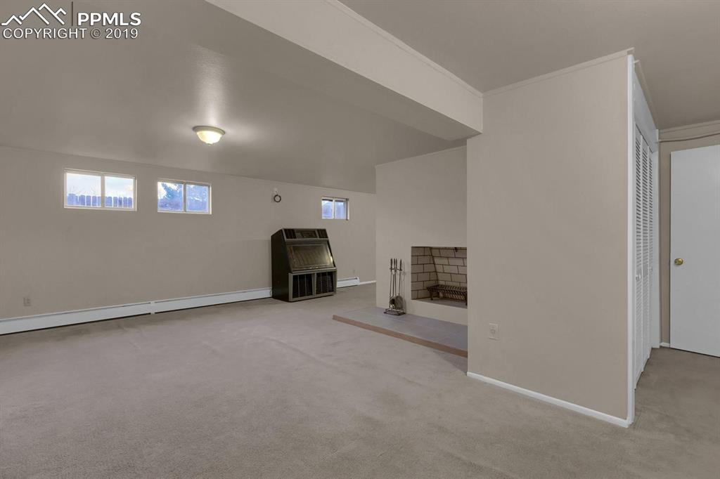 Oversized family room in basement with wood burning fireplace and additional storage room