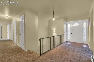 Entryway into home and hallway leading to main level bedrooms
