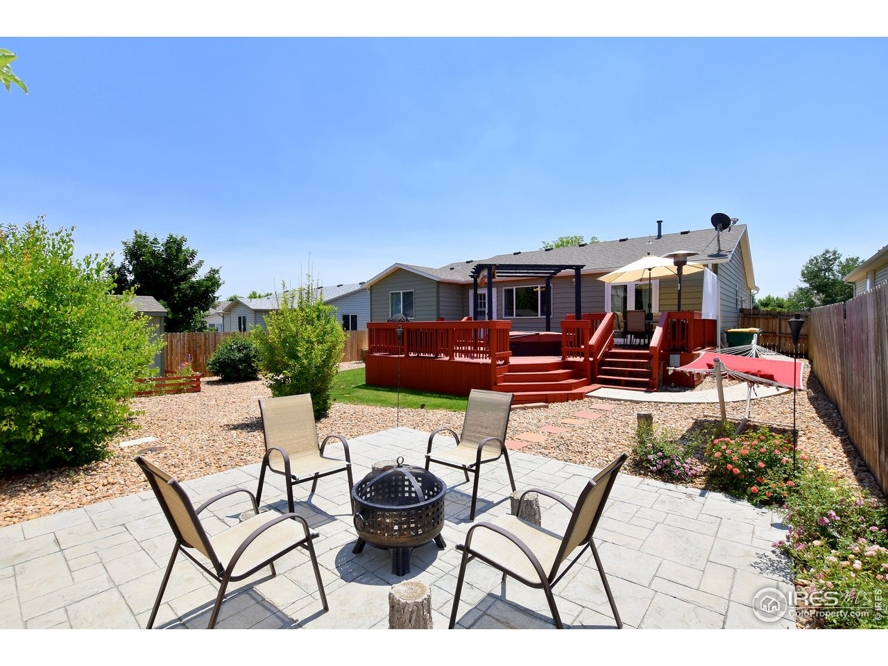 Park Like Fenced Back Yard with Stamped Concrete Patio, Deck with Hot Tub, Trees and Lots of Flowers