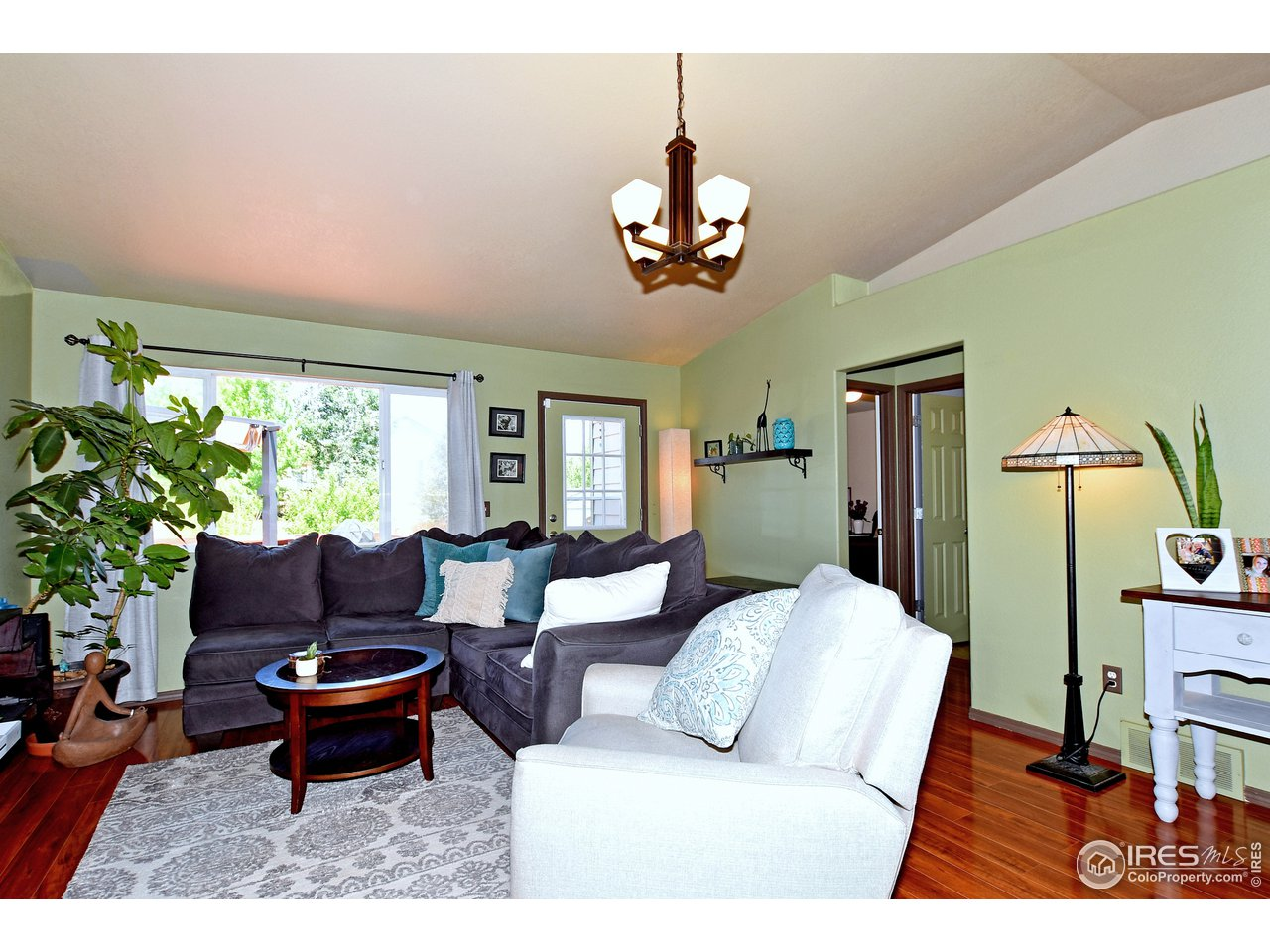 Vaulted great room with large Windows and door to deck.    Beautiful laminate floors