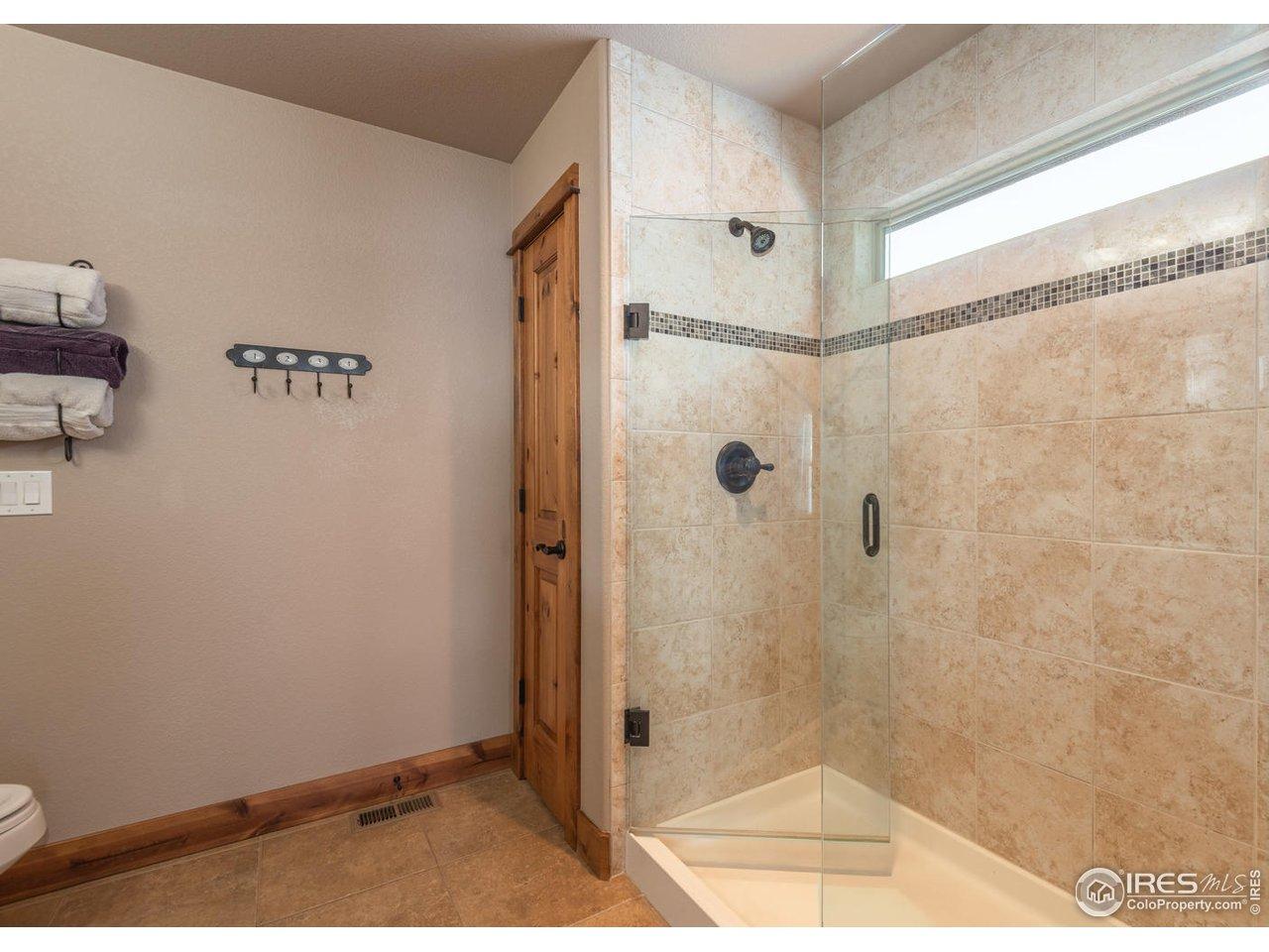 Tiled master shower with frameless door