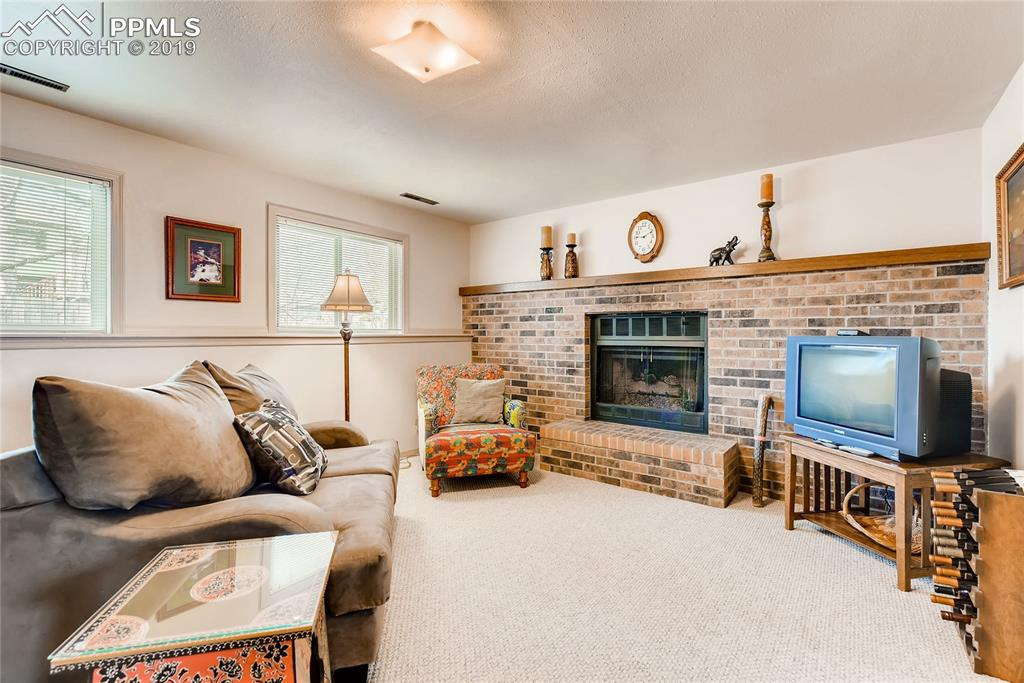 Lower level family room with full wall brick fireplace