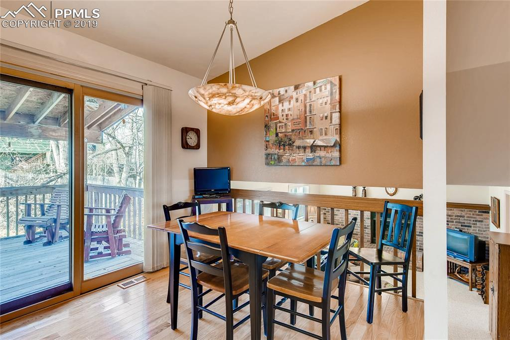 Hardwood floors eat-in Kitchen with custom lighting and walks out to covered dec