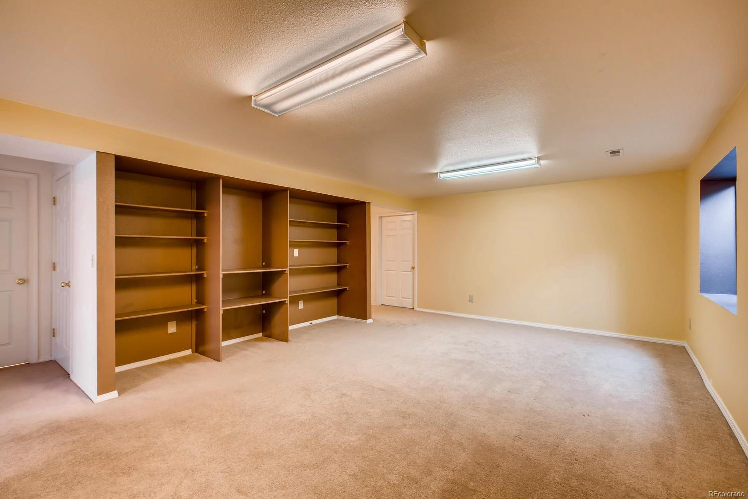 Large basement family room with built-in shelving